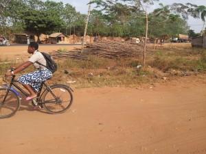 Elève fille sur vélo allant à l'école à Vakon, Porto Novo, Bénin