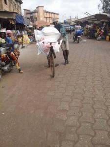 Un cycliste transportant des sacs de farine de blé, au marché Ouando, Porto Novo, Bénin