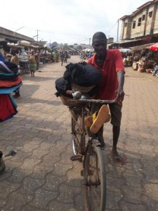 Un cycliste transportant duu poisson fumé, au marché Ouando, Porto Novo, Bénin